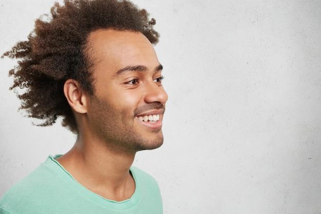 Seitliches porträt eines afroamerikanischen fröhlichen mannes mit knackigem haar, lächelt sanft