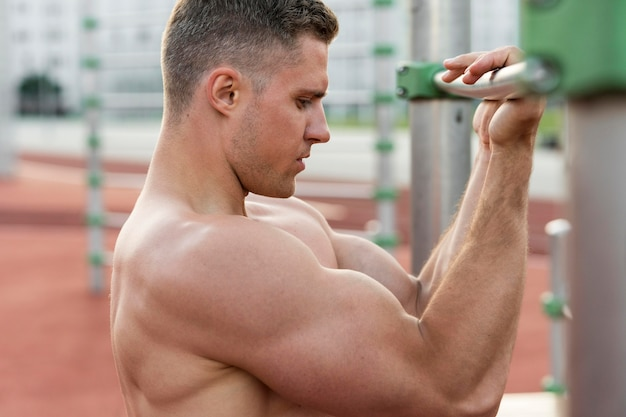 Seitwärts athletischer mann, der hemdlos trainiert