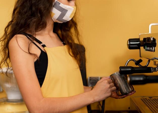 Seitwärts barista trägt eine gesichtsmaske beim kaffeekochen
