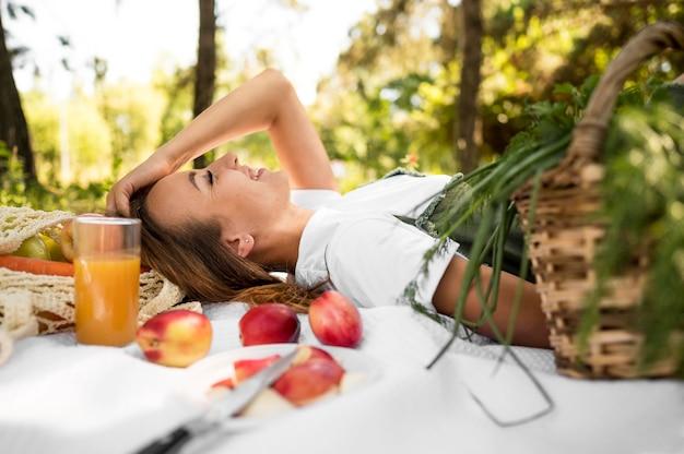 Seitwärts frau, die ein picknick mit gesunden snacks hat