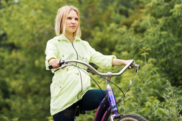 Seitwärts frau, die ihr fahrrad fährt