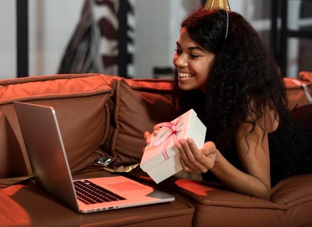 Seitwärts frau, die ihr geschenk zeigt, während video-chat auf einer silvesterparty