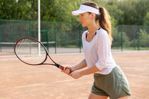 Seitwärts frau, die tennis spielt