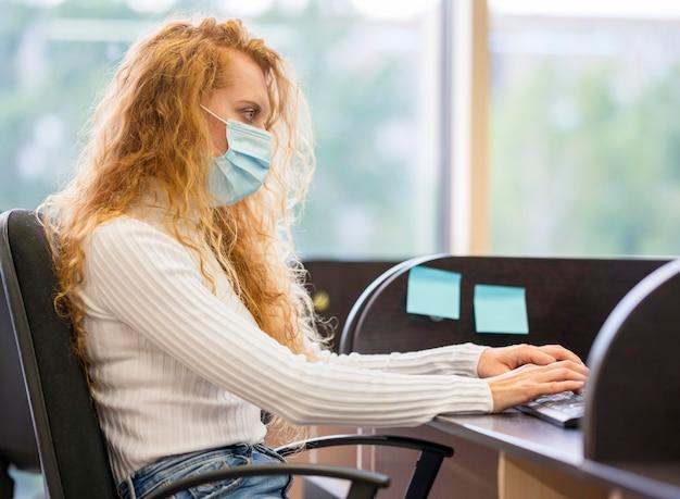 Seitwärts geschäftsfrau, die medizinische maske trägt