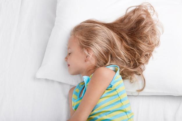Seitwärts geschossenes kleines kind trägt nachtwäsche, ist tief im schlaf, ruht im bett, liegt auf weißem bett, genießt schlafenszeit, ruht nach aktiven spielen im freien mit freunden, nickerchen im schlafzimmer. kinderkonzept