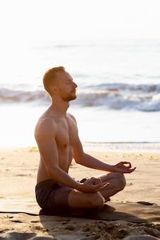 Seitwärts hemdloser mann, der am strand meditiert