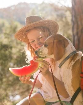Seitwärts hund und frau, die eine scheibe wassermelone essen