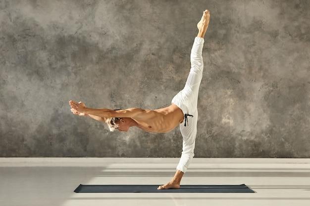 Seitwärts innenaufnahme eines sportlichen muskulösen mannes mit nacktem oberkörper, der urdhva prasarita eka padasana auf der matte tut, muskeln dehnt und stärkt, sich parallel zum boden nach vorne beugt, beine gespalten