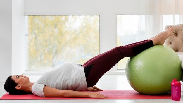 Seitwärts junge schwangere frau, die auf fitnessball ausübt