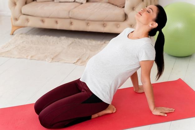 Seitwärts junge schwangere frau, die auf fitnessmatte ausübt