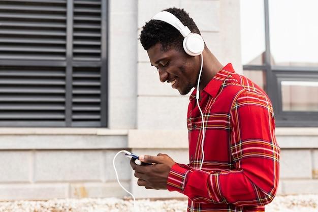 Seitwärts junger erwachsener im roten hemd, das musik hört