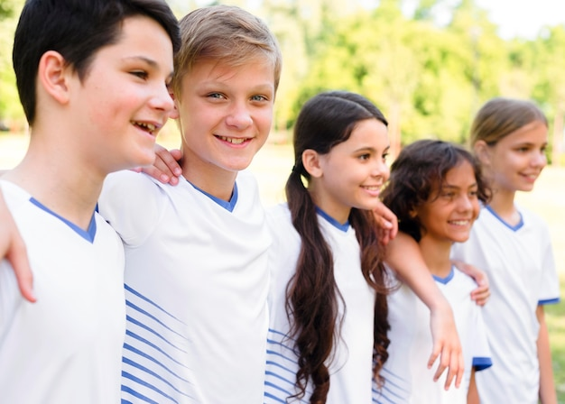 Seitwärts kinder in sportbekleidung halten sich gegenseitig