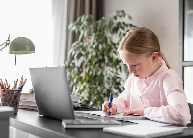 Seitwärts kleines mädchen, das an online-klasse teilnimmt