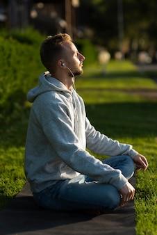 Seitwärts mann, der am strand meditiert