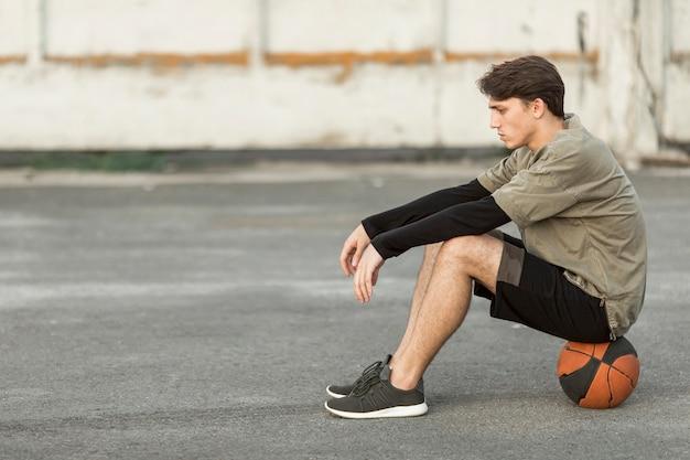 Seitwärts mann, der auf einem basketball sitzt