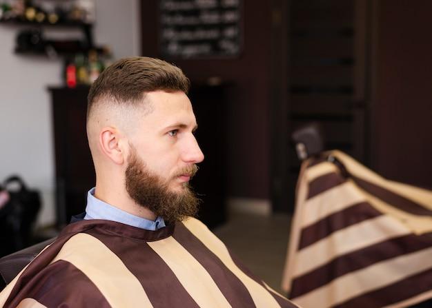 Seitwärts mann, der auf einen neuen haarschnitt wartet