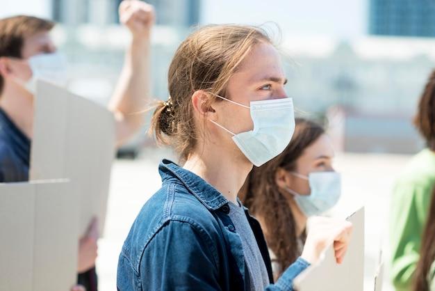 Seitwärts mann, der protestiert und medizinische maske trägt