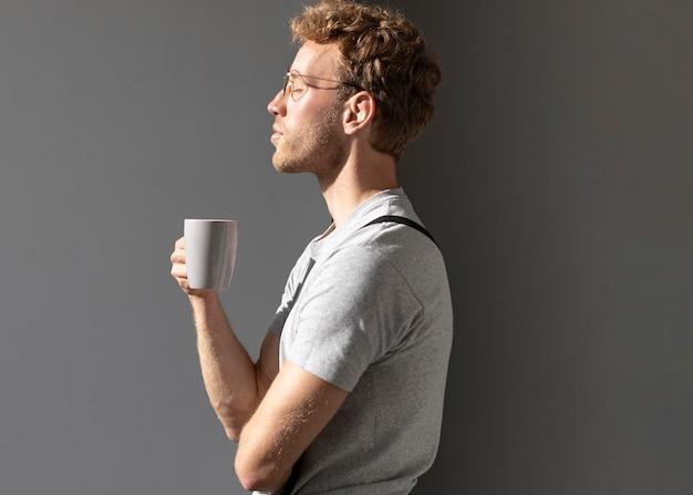 Seitwärts mann, der seinen kaffee trinkt