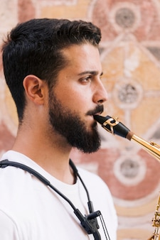 Seitwärts mannportrait, welches das saxophon spielt