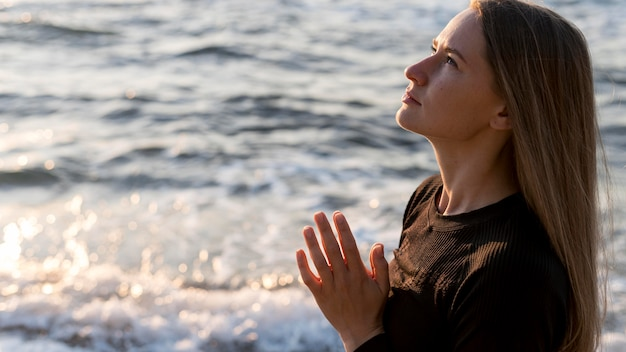Seitwärts meditierende frau am strand