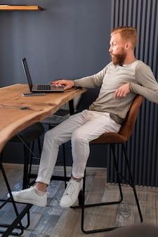 Seitwärts moderner mann, der am laptop arbeitet