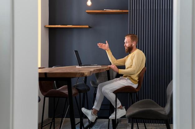 Seitwärts moderner mann, der an einem modernen büro arbeitet