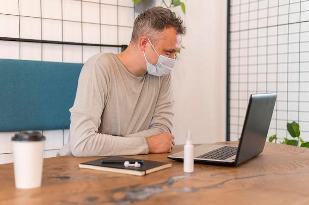 Seitwärts moderner mann mit der medizinischen maske, die arbeitet
