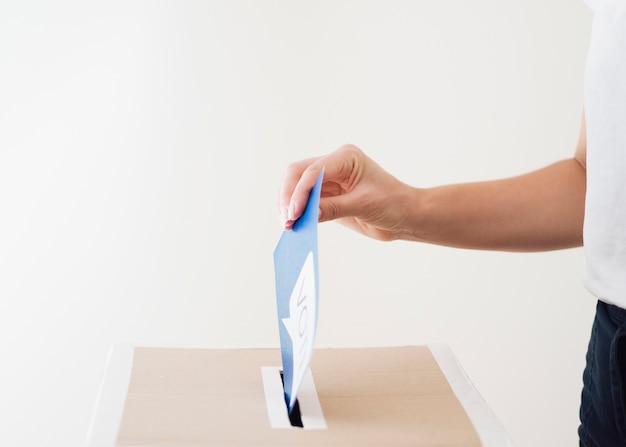 Seitwärts person, die stimmzettel in kasten einsetzt