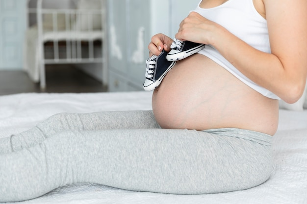 Seitwärts schwangere frau, die mit kleinen schuhen spielt