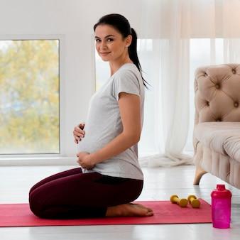 Seitwärts schwangere frau, die yoga macht