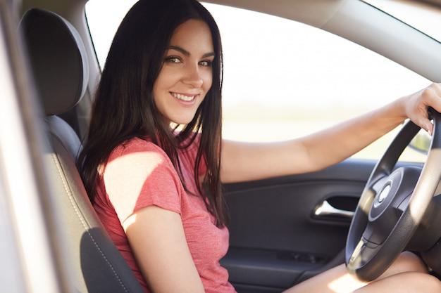 Seitwärtsaufnahme der angenehm aussehenden brünetten frau sitzt in ihrem eigenen autolehrer