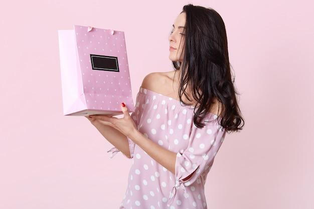 Seitwärtsaufnahme der brünetten ernsten jungen frau schaut auf geschenktüte, trägt modisches sommerkleid, genießt es, geschenk zu erhalten, posiert auf rosa. frau macht einkaufen, steht drinnen