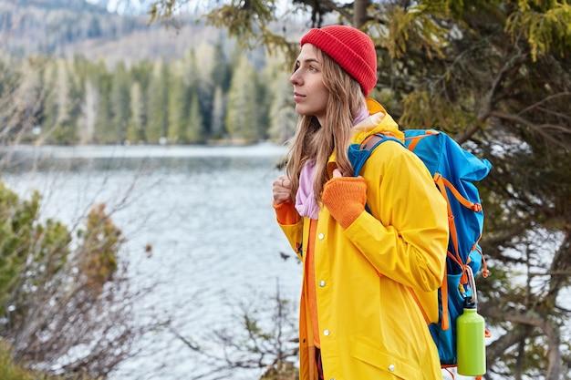 Seitwärtsaufnahme der schönen weiblichen reisenden steht mit rucksack