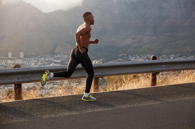 Seitwärtsaufnahme des athletischen mannes legt lange strecke zurück, läuft auf leerer straße, läuft am frühen morgen auf hügeligem weg, trainiert auf der straße, zeigt seinen schlanken körper, der stark ist. bestimmungskonzept