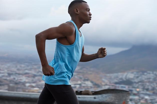 Seitwärtsaufnahme des sportlichen dunkelhäutigen läufers trägt blaue weste, nimmt am triathlonrennen teil, hat fitness-lebensstil, modelle gegen verschwommene sicht nach draußen mit steinen, fotografiert in schneller bewegung.