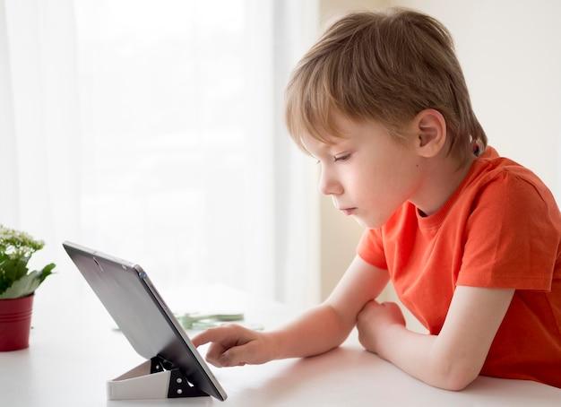 Seitwärtsjunge, der ein digitales tablett benutzt