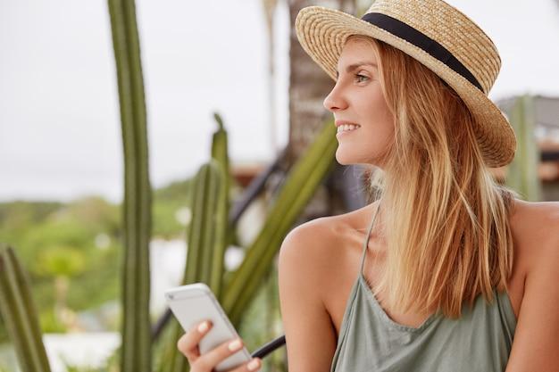 Seitwärtsporträt der glücklichen reizenden frau mit verträumtem positivem blick, trägt sommerhut