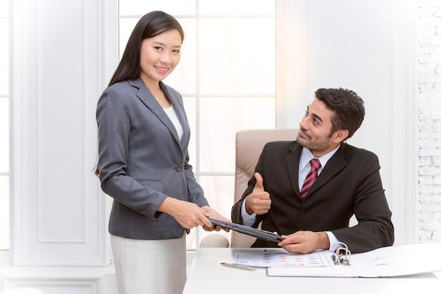 Sekretär, der im büro steht, das ihrem chef ein dokument darstellt
