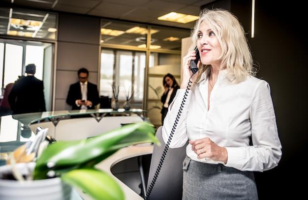 Sekretär, der in einem büro ans telefon geht