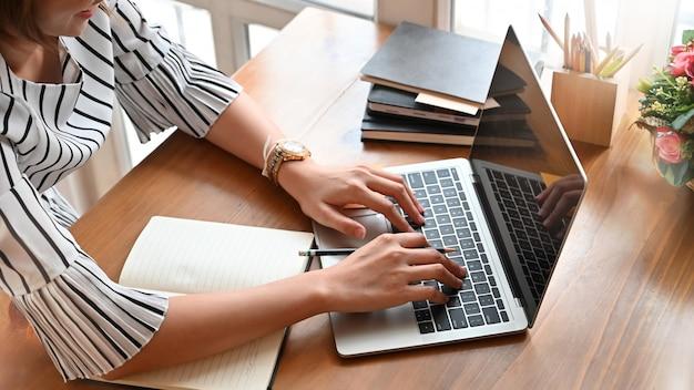 Sekretärfrau, die laptop-computer auf arbeitsschreibtisch mit geerntetem schuss verwendet.