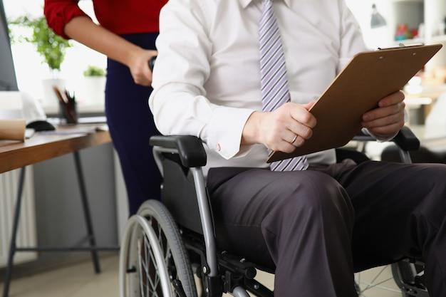 Sekretärin rollt ceo im rollstuhl mit dokumenten und berichten in den händen