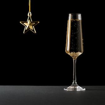 Sekt in einem hohen glas und einem goldenen stern auf schwarz