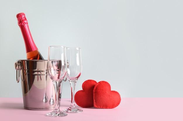 Sekt, rote herzen und weingläser für die valentinstagsparty zu zweit. grußkarte.