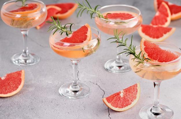 Sektbecher mit einer grapefruitscheibe und einem rosmarinzweig