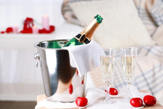 Sektflasche im eimer, gläser und rosenblätter zum feiern des valentinstags