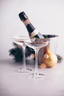 Sektflasche im eimer mit eis, gläsern und weihnachtsdekorationen