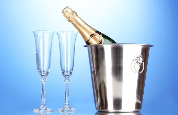 Sektflasche im eimer mit eis und gläsern auf blauer oberfläche