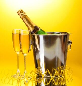 Sektflasche im eimer mit eis und gläsern champagner, auf gelber oberfläche