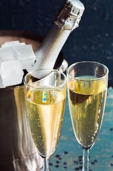 Sektflasche im eimer mit eis und gläsern champagner