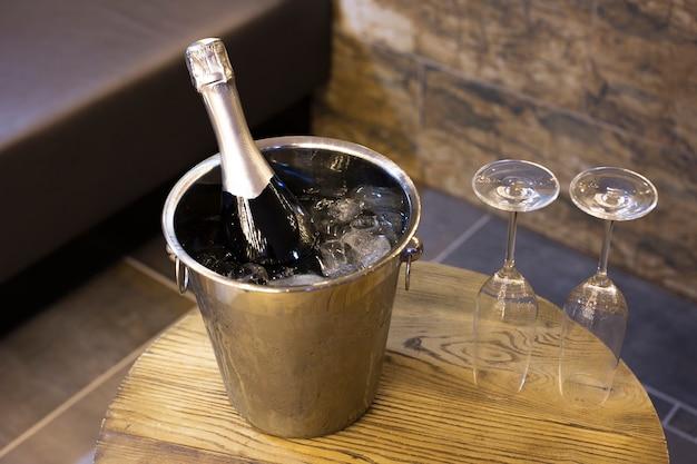 Sektflasche im kühleimer mit eis und zwei sektgläsern auf holztisch romantisch